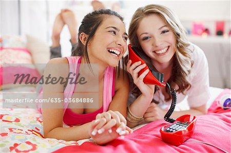 Teenage girls talking on telephone in bedroom