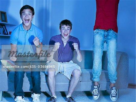 Shouting teenage boys watching television
