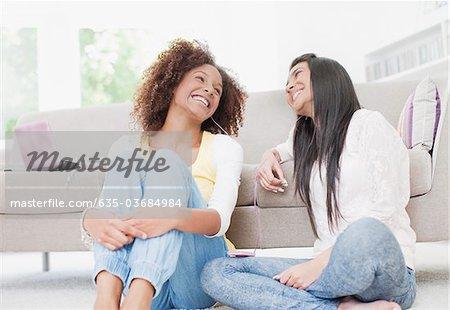 Smiling teenage girls sitting on living room floor