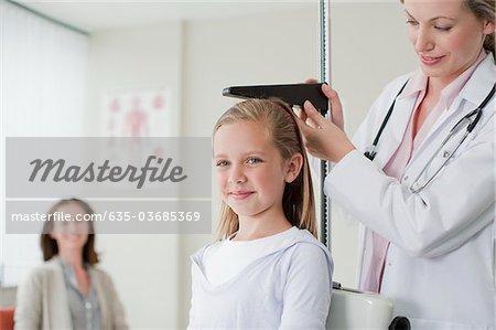 Doctor measuring patient's height in doctor's office