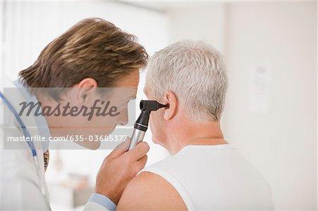 Doctor examining patient's ear in doctor's office