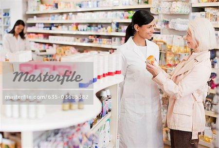 Pharmacist talking to customer in drug store