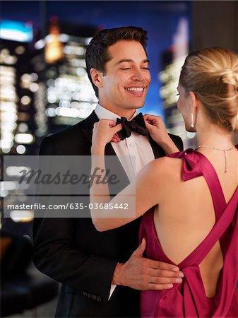 Elegant woman fixing husband's bowtie