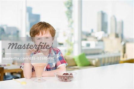 Boy putting cherry on ice cream sundae
