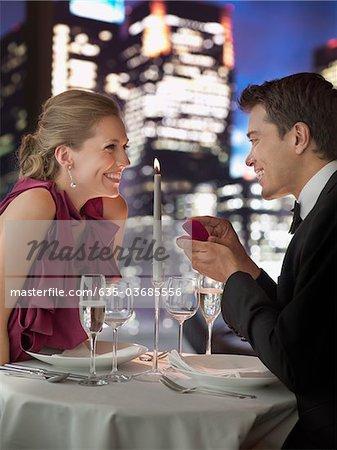 Man in tuxedo proposing engagement to girlfriend