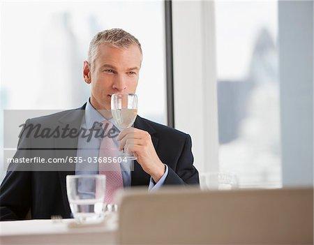 Businessman drinking white wine in restaurant