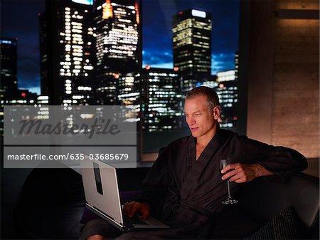 Man in bathrobe drinking wine and using laptop