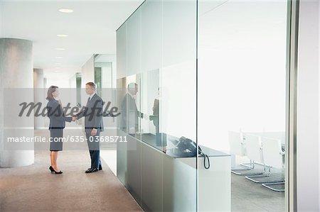 Business people shaking hands in modern office corridor
