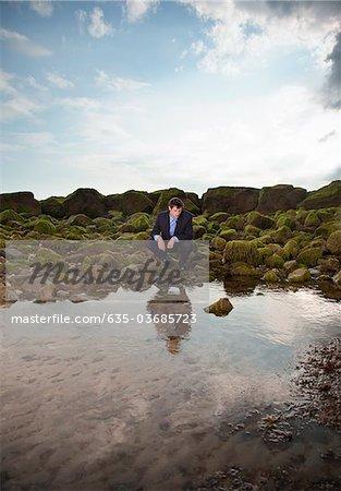 Businessman squatting near ocean tide pool