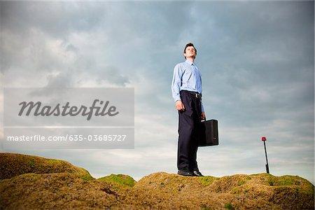 Businessman standing on rocks