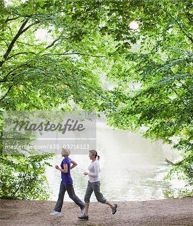 Women jogging together near lake