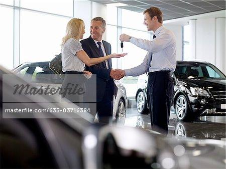 Salesman handing couple keys to new car in showroom