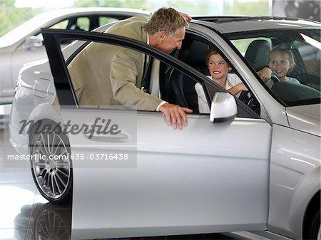 Salesman talking to children in new car in showroom