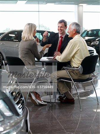 Salesman handing car key to couple in automobile showroom