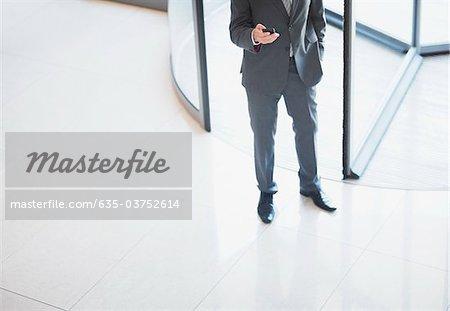 Businessman holding cell phone near revolving doors