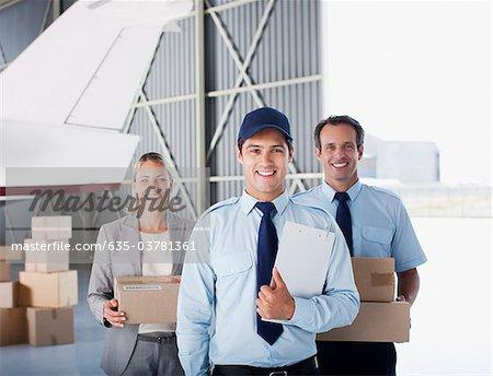 Supervisor and workers standing in hangar
