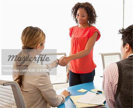 Businesswomen shaking hands in conference room
