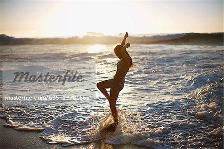 Woman standing in ocean waves