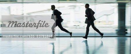 Businessmen running in airport