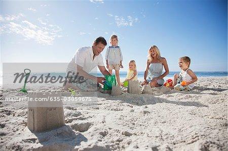 Family making sand castles on beach