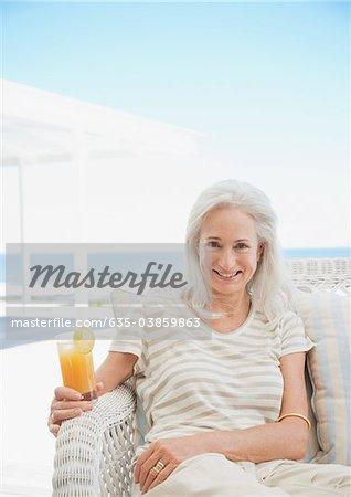 Senior woman drinking cocktail on patio