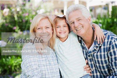 Grandparents hugging granddaughter