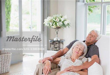 Senior couple sleeping on sofa in living room