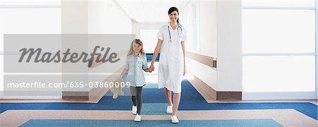 Nurse and girl patient in hospital corridor