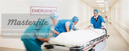 Doctors pushing patient on gurney down hospital corridor