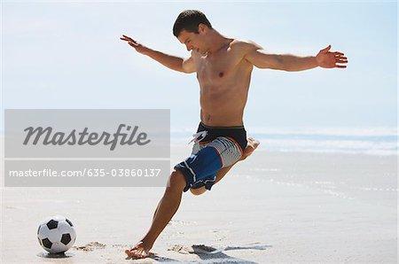 Man kicking soccer ball on beach