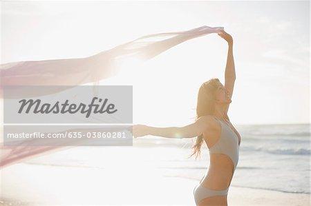 Woman holding sarong overhead on beach