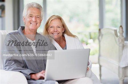 Senior couple in bathrobes using laptop