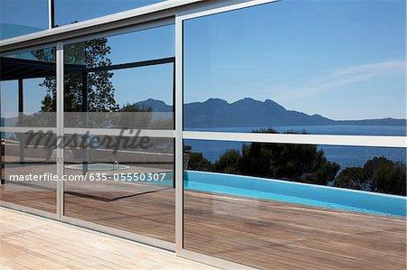 Windows reflecting infinity pool and skyline