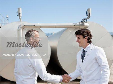 Technicians shaking hands outdoors