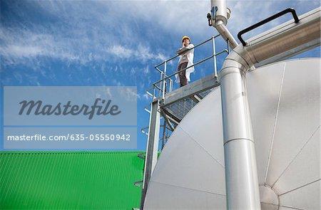 Scientist standing on walkway on tanks