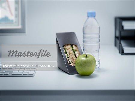 Sandwich, apple and water on office desk