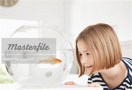 Girl examining goldfish in fishbowl