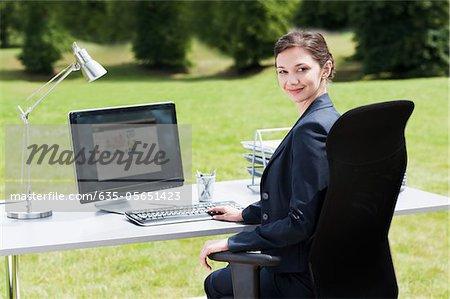 Businesswoman sitting at desk in field