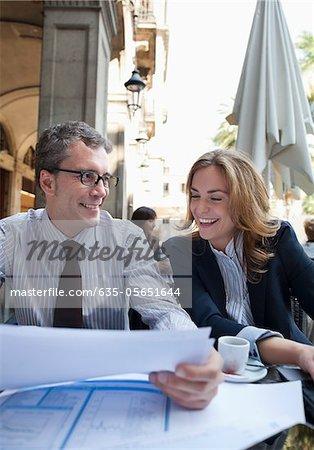 Business people working in sidewalk cafe