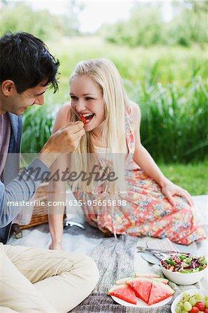 Man feeding woman strawberry on picnic blanket in park