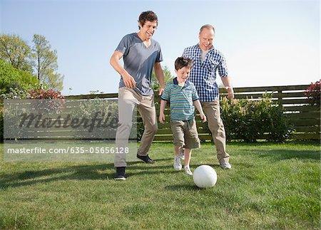 Multi-generation family playing soccer in backyard