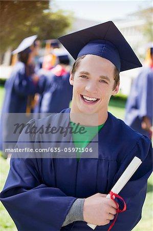 Smiling graduate carrying diploma