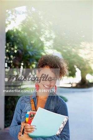 Smiling student carrying folder