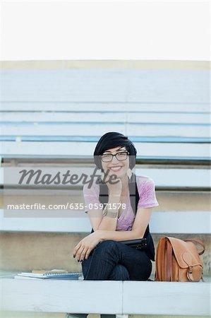 Smiling student sitting on bleachers