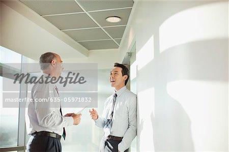 Smiling businessmen talking in office