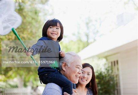 Older man carrying grandson on shoulders