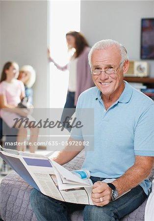 Older man reading newspaper on bed