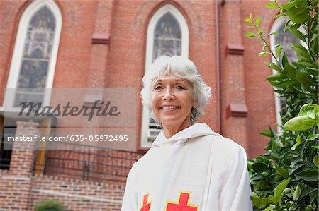 Smiling reverend standing outside church