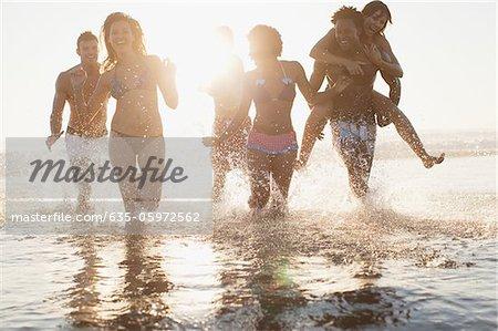 Friends running in waves on beach