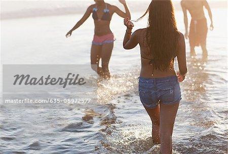 Women walking in waves at beach